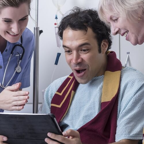 A surprised man in hospital gown and sports scarf with two nurses looking down at an iPad watching sports
