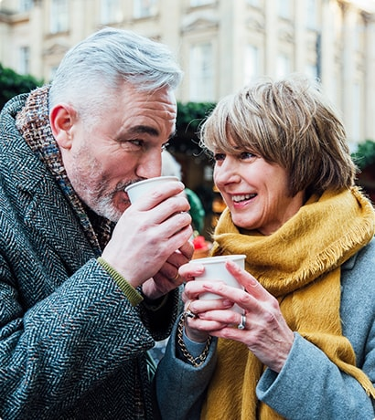 Older couple drinking warm drinks in cold weather
