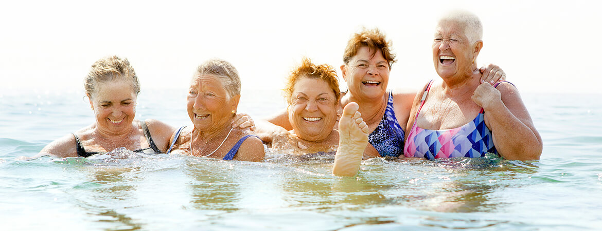 Group of women laughing together while in the water.