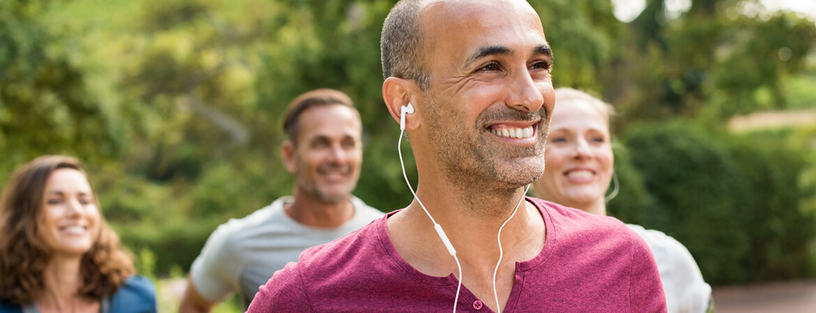 A group of friends exercising with man in the foreground listening to music through his headphones.
