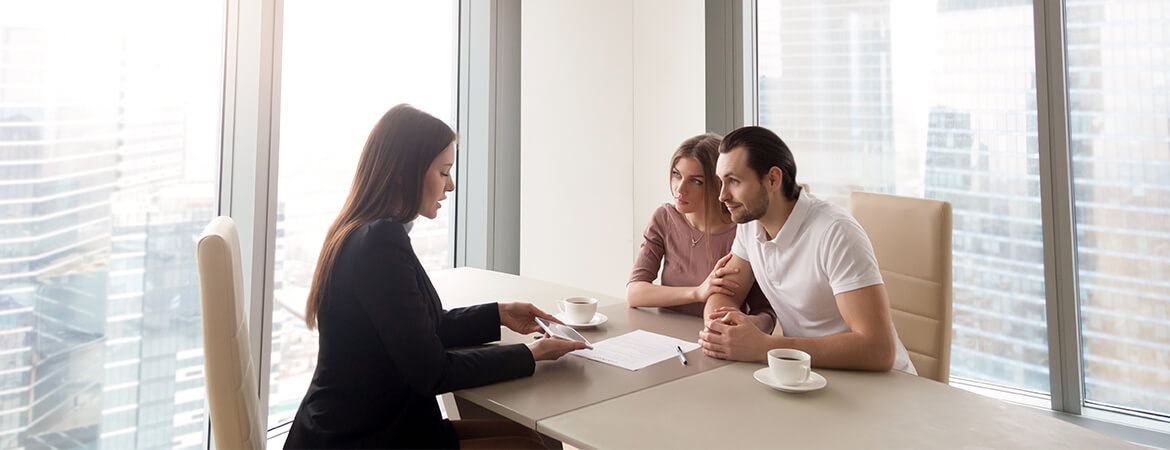 A couple meeting with a broker in a city office building.