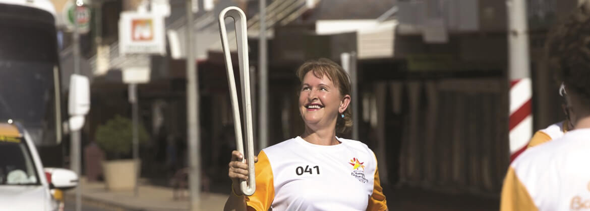 QSuper female member holding the Commonwealth Games Queen's Baton and smiling