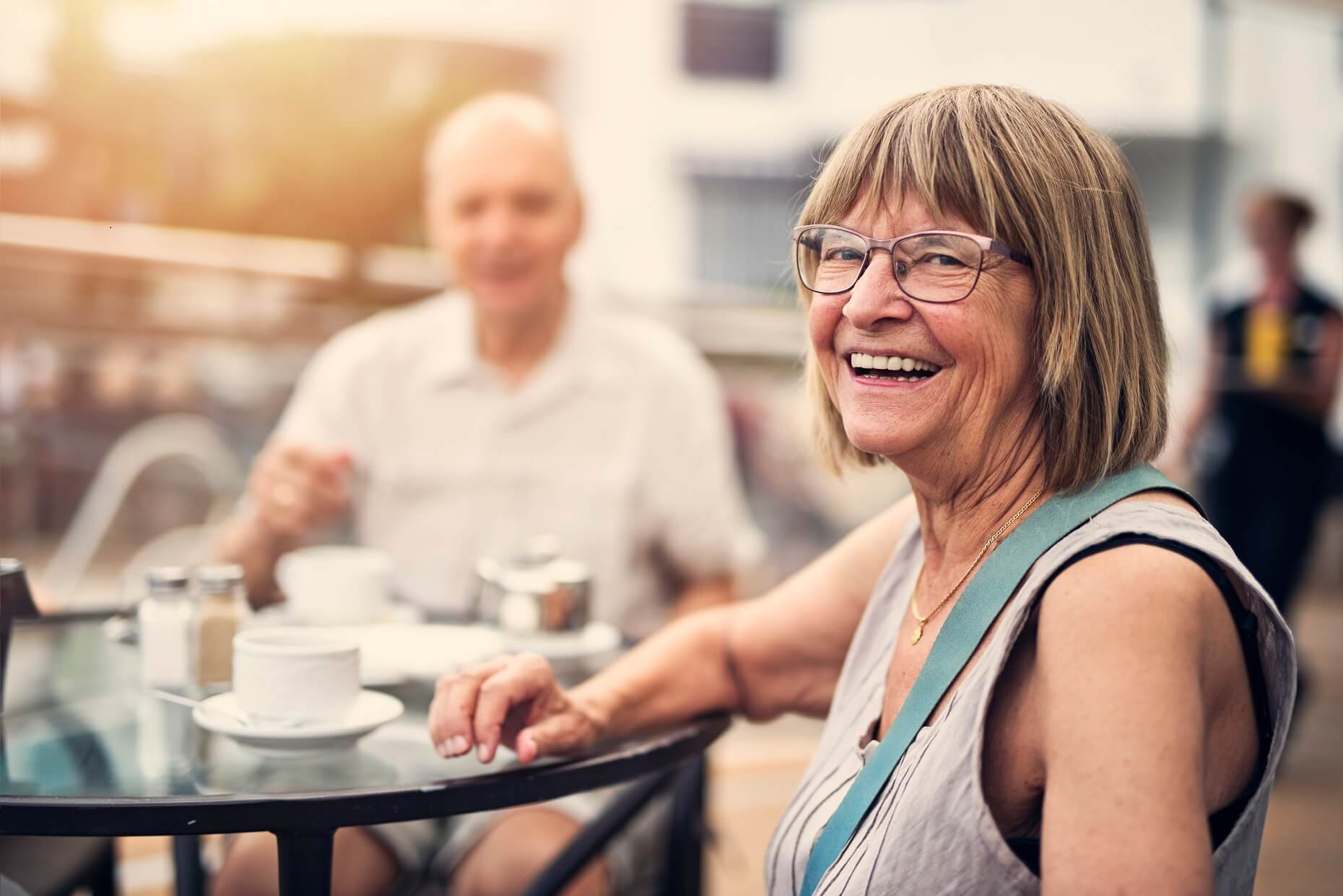 Elderly woman with glasses smiling, sitting a table with coffee cups and a man in the background