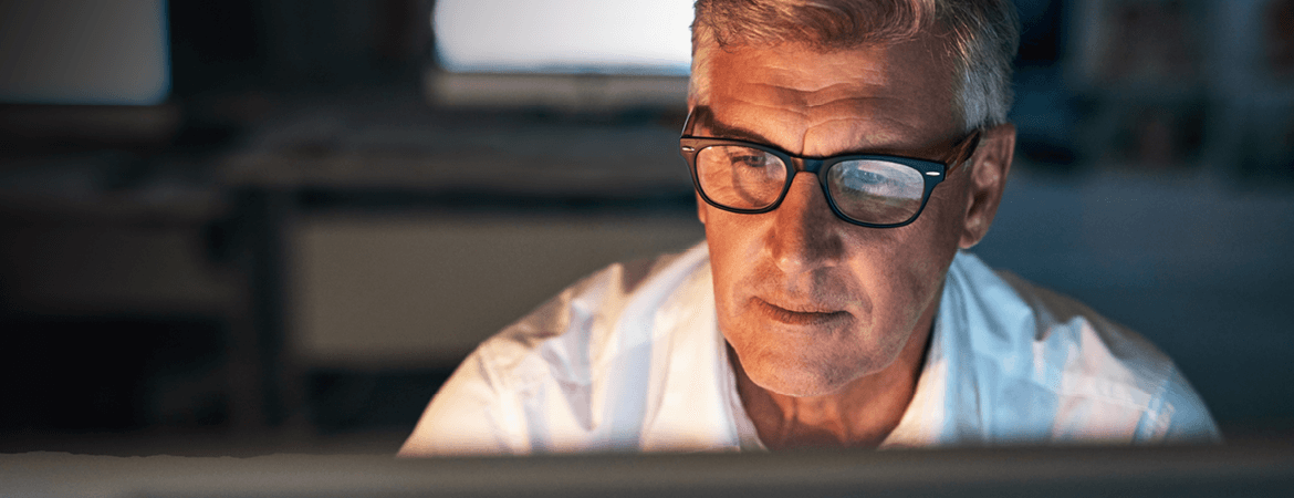 A grey-haired man in a white shirt wearing black rimmed glasses working on his computer.