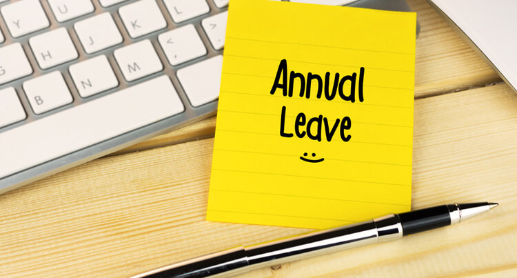 post-it note with annual leave written on it stuck to an office desk near a keyboard