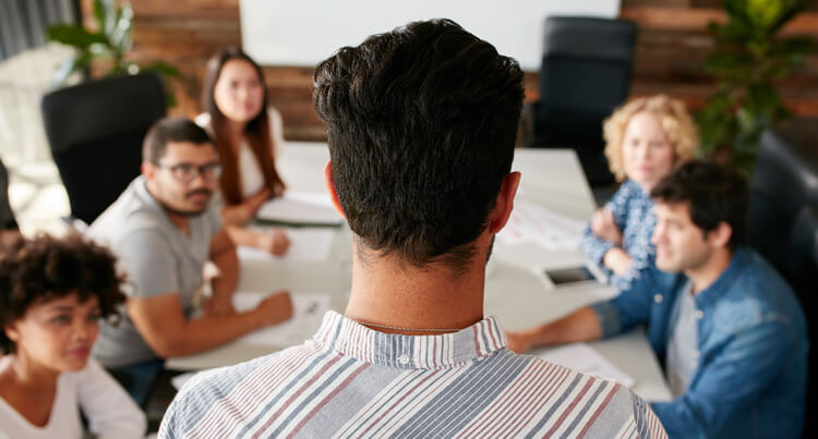 The back of a man's head with short brown hair and a red, blue and white stripped shirt as he stands in front of a group of three women and two men in a meeting room