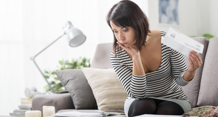 Lady in her living room reviewing bills that she has just received