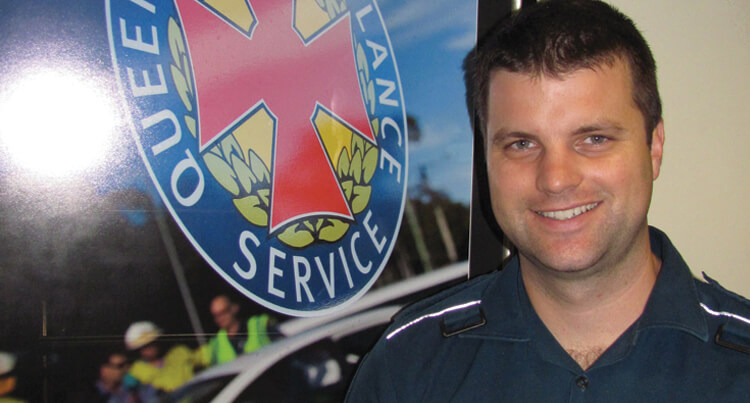 Man in a uniform smiling and standing in front of the Queensland Ambulance logo