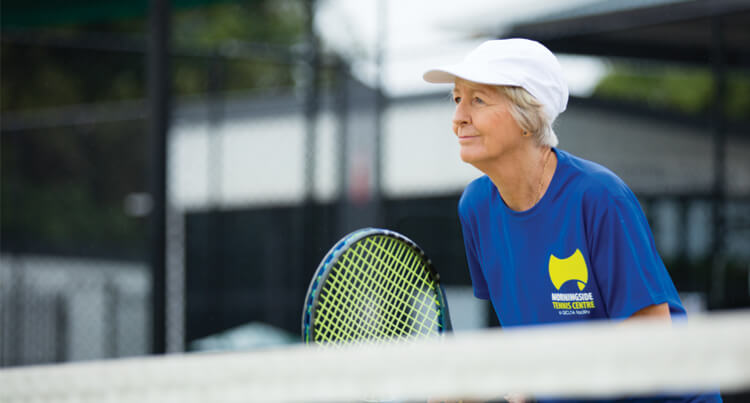 A lady playing tennis who is positioned at the net and waiting to volley the ball