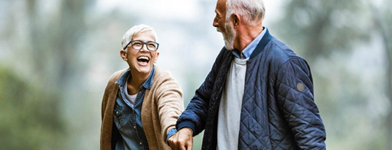 Elderly couple smiling holding hands walking