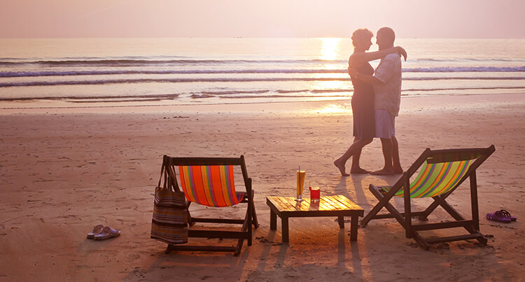 Couple in each others arms on the beach waiting for the sunset