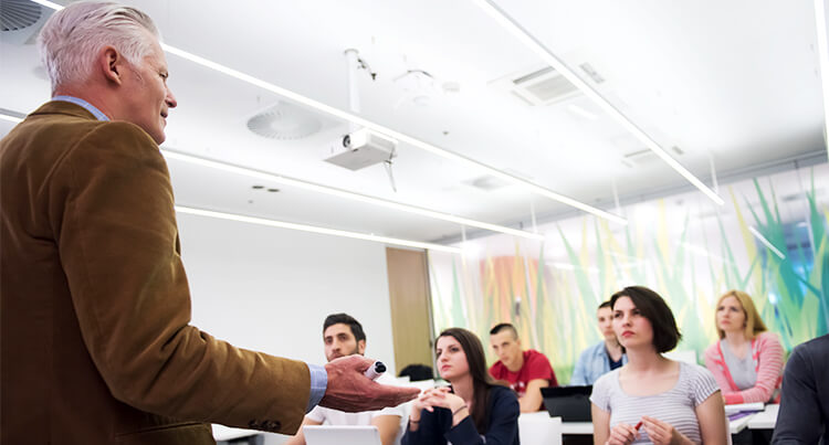 Lecturer standing at the front of the classroom and teaching his students