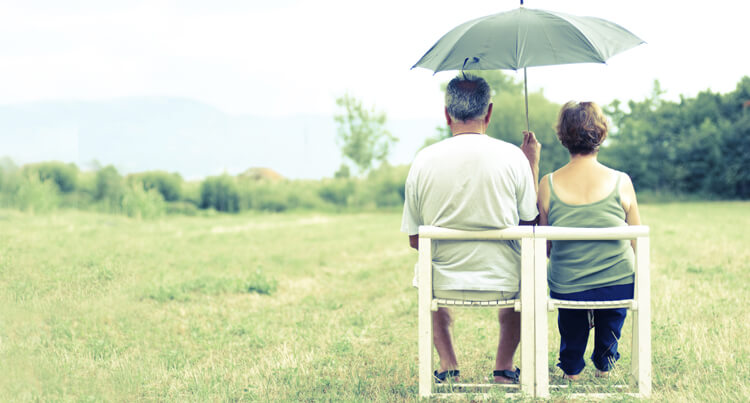 Couple sitting in chairs in an open grass field with an open umbrella