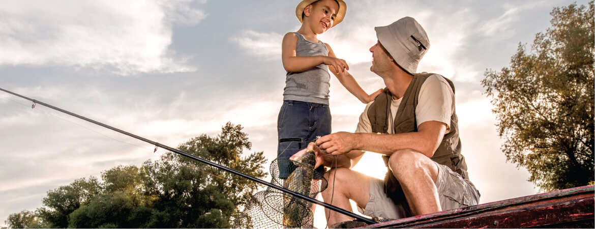 Small boy and man in a vest wearing hats looking at each other and holding a fishing rod and net while sitting in a boat